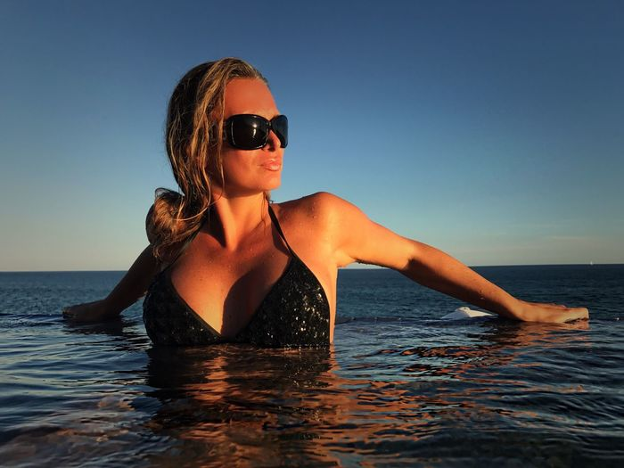 Sensuous woman in infinity pool by sea against clear blue sky