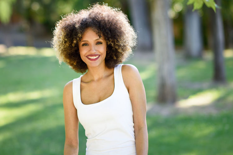 Young woman, afro hairstyle, smiling in urban park Beautiful Woman Curly Hair Day Focus On Foreground Front View Happiness Leisure Activity Lifestyles Looking At Camera Nature One Person Outdoors Portrait Real People Smiling Tree Urban Water Young Adult Young Women