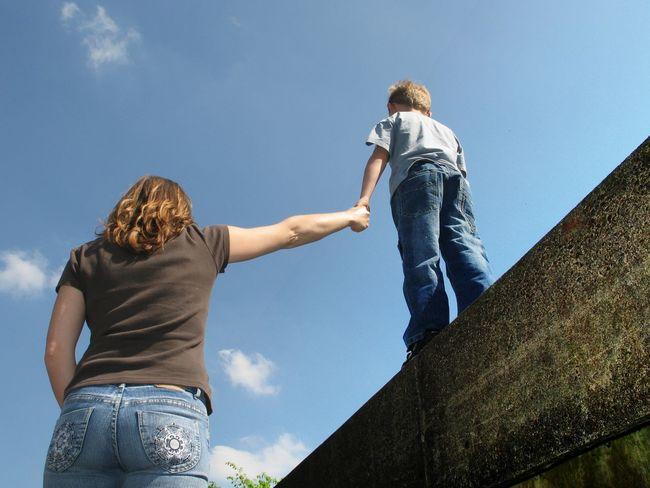 Mutter hält ihrem Sohn die Hand um ihn zu sichern weil er auf einer hohen Mauer geht Absichern Festhalten Gefahr Gefährlich Halten Hand Hand Halten Himmel Und Wolken Halt Kind Mauer Mother And Son Mutter Sichern Sohn  Symbol Symbolbild Symbols Wall