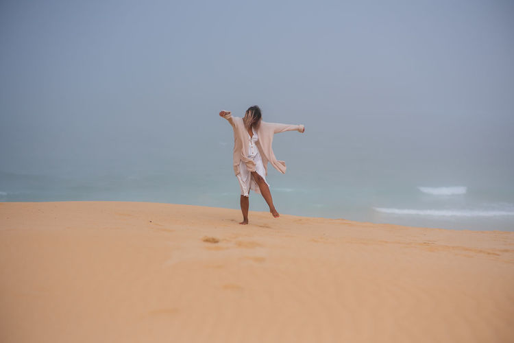 Rear view of person on beach against sky