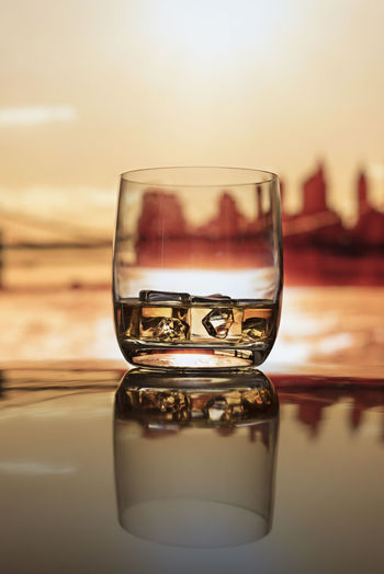 Whiskey on ice resting on reflective table with Manhattan silhouetted at sunset in the background. Brooklyn Bridge / New York Happy Hour Ice Manhattan Scotch Whisky Silhouette Skyline Travel Abuse Alcoholism Bourbon Close-up Day Golden Hour Indoors  Lifestyles Luxury Nature No People Reflection Rocks Sky Tequila Water Whiskey