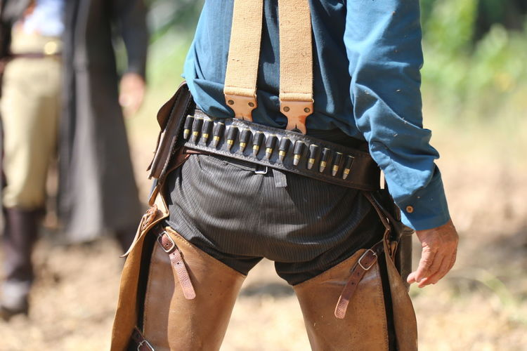 One Person Focus On Foreground Midsection Standing Day Real People Holding Clothing Nature Sunlight Lifestyles Men Land Outdoors Leisure Activity Belt  Weapon Human Body Part Gun Leather Uniform