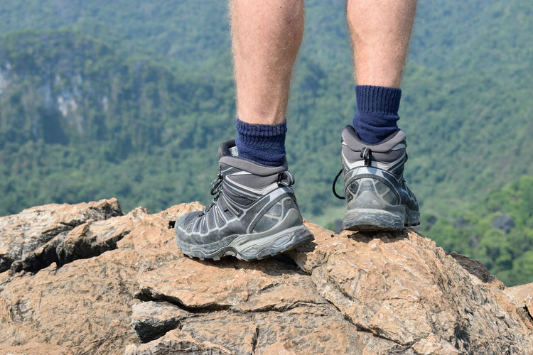 Low section of man standing on mountain peak