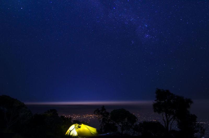 Illuminated tent against star field sky at night