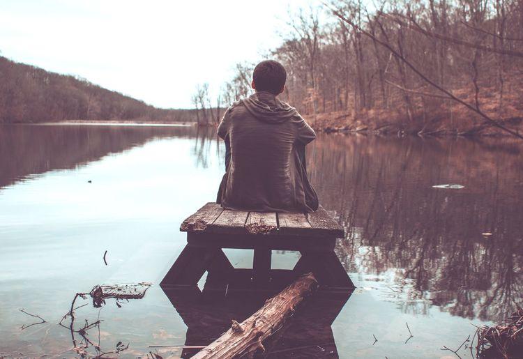 Rear view of man looking at lake