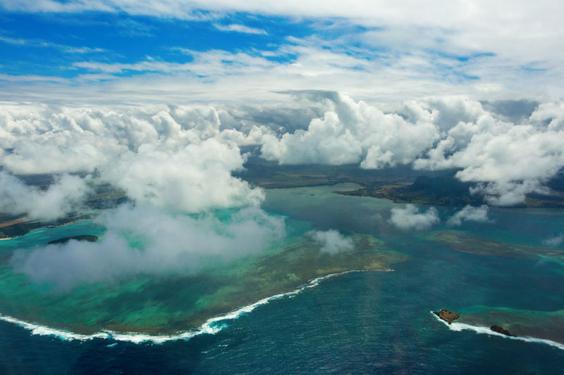 Aerial view of seascape against cloudy sky