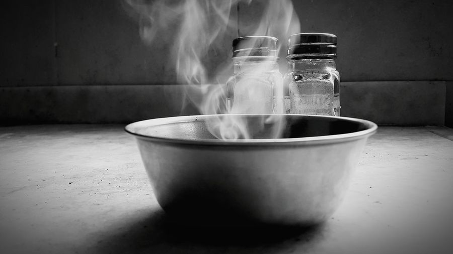 Smoke in bowl with salt and pepper shaker in background