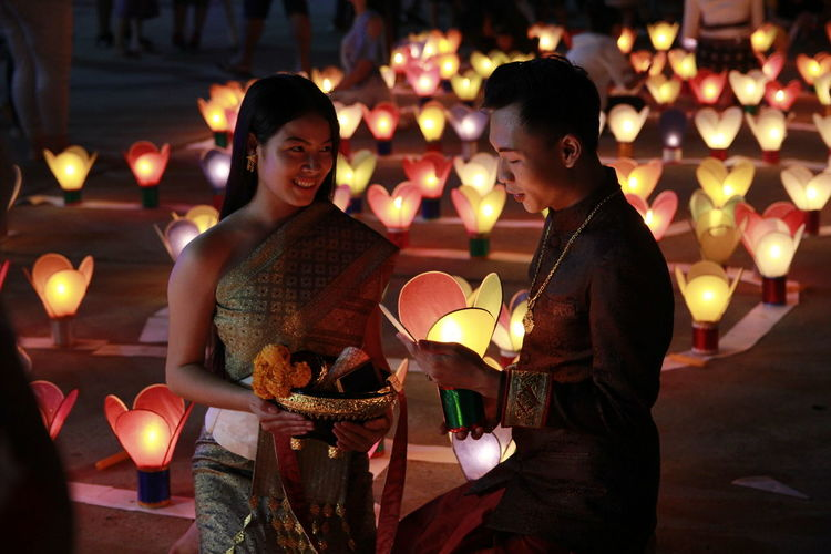 Young couple with illuminated lanterns at night