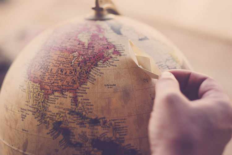 Small paper boat over the world map. travel destination , fantastic dream. human hand Human Hand Human Body Part Hand Holding One Person Close-up Selective Focus Indoors  Text Finance Business Paper Paper Currency Currency Wealth Map Communication Western Script Savings Boat World Round Fantasy Hope Happiness