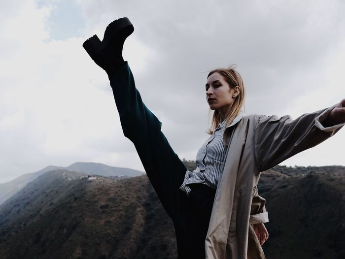 Woman kicking while standing on mountain against sky
