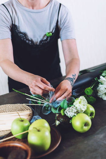 Midsection of man holding vegetables on cutting board