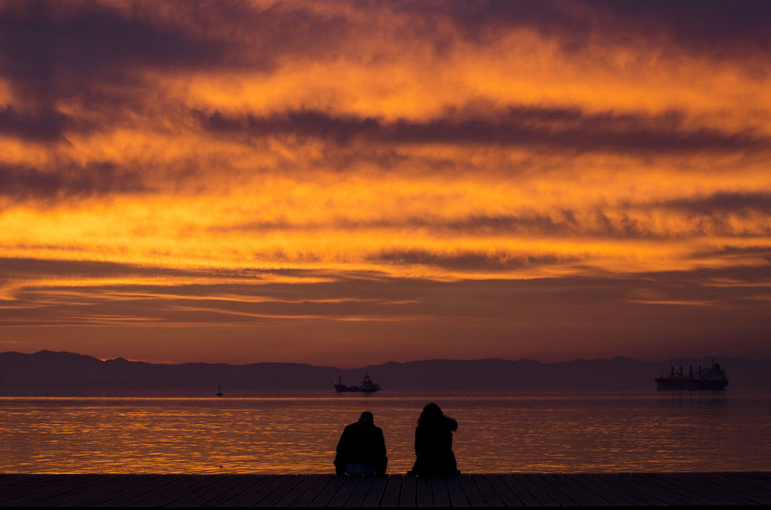 Love Romance Beauty In Nature Bonding Cloud - Sky Leisure Activity Lifestyles Men Nature Orange Color Outdoors People Real People Scenics Sea Silhouette Sitting Sky Sunset Togetherness Tranquil Scene Tranquility Two People Water Women