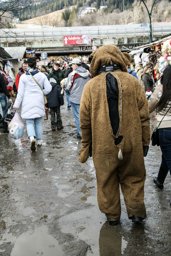 A person wearing a bear costume trudges slowly along wet muddy ground in a busy city scene Adult Broken City Crowd Day Drudgery Entertainment Fancy Dress Forlorn Job Lifestyles Men Menial Mud Outdoors Poland Real People Rear View Sad Standing Tourist Trudge Through EyeEmNewHere Wet Winter
