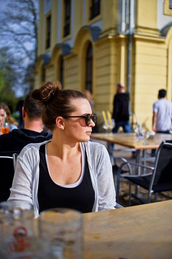 Woman in sunglasses sitting at cafe