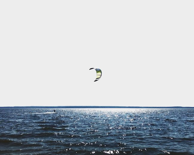 Person paragliding over sea against clear sky
