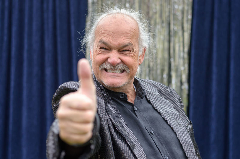 Portrait of smiling senior entertainer gesturing thumbs up at event