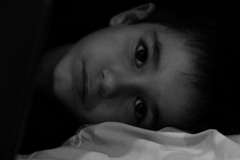 Portrait Of Boy Lying In Darkroom