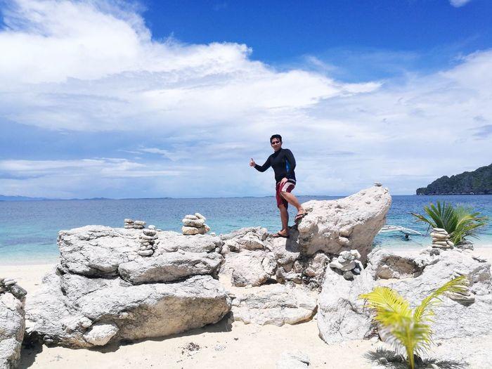 Man standing on rocks by sea against sky