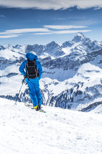 Rear view of person on snowcapped mountain