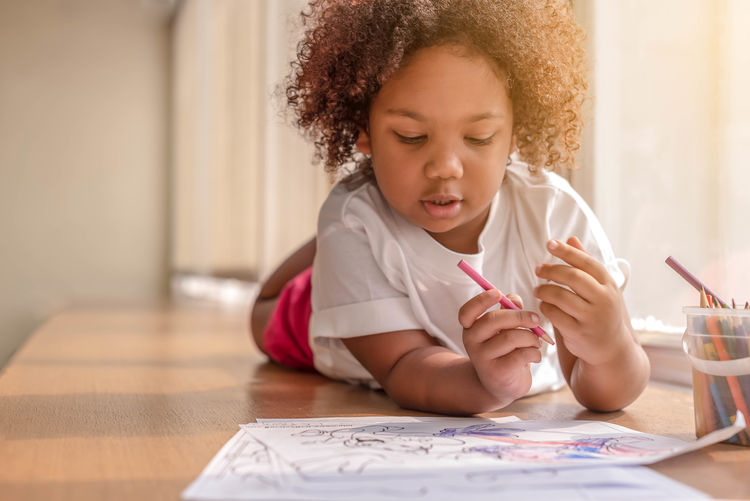 Leisure Activity Looking Down Innocence Hairstyle Looking Real People Sitting Curly Hair One Person Lifestyles Child Childhood Headshot Table Women Indoors  Front View Girls Females