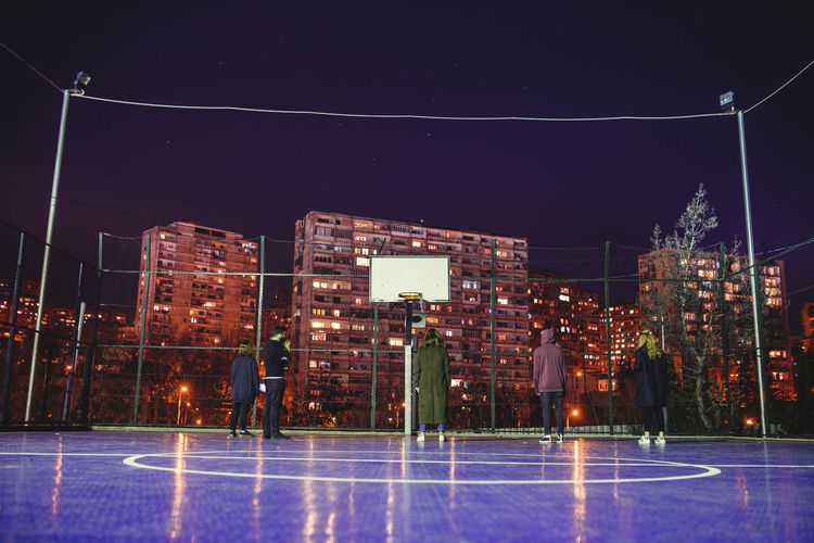 Adult Adults Only Architecture Basketball Hoop Building Exterior City Cityscape Court Full Length Ice Hockey Ice Rink Illuminated Match - Sport Night Outdoors People Sky Sport Star - Space Taking A Shot - Sport Winter Sport