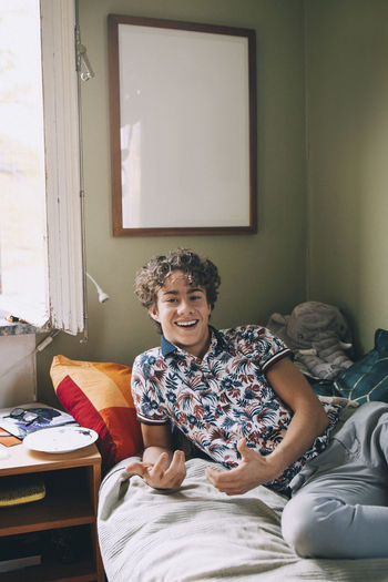 Portrait of a smiling young man sitting on bed