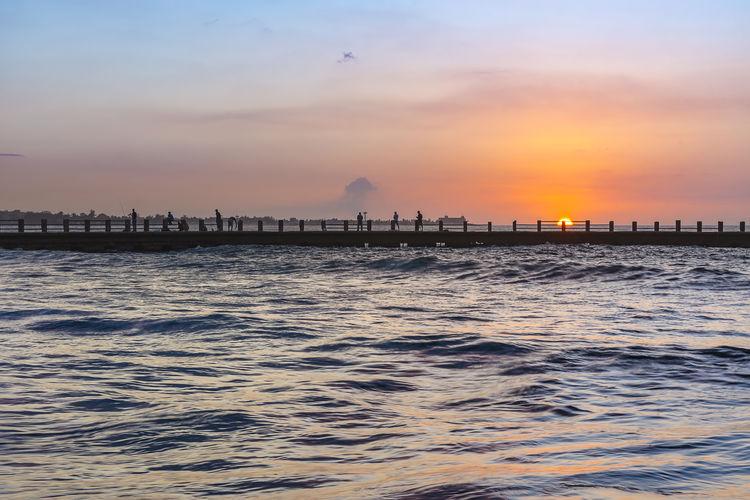 Catching rays Fishermen Fishing Water Sea Sunset Silhouette Sun Tide Romantic Sky Seascape Dramatic Sky Coast Moody Sky Coastal Feature Atmospheric Mood Horizon Over Water Low Tide