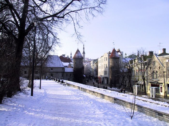 Snow covered houses and buildings against sky