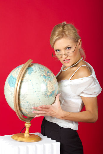 Portrait of businesswoman standing by globe against red background