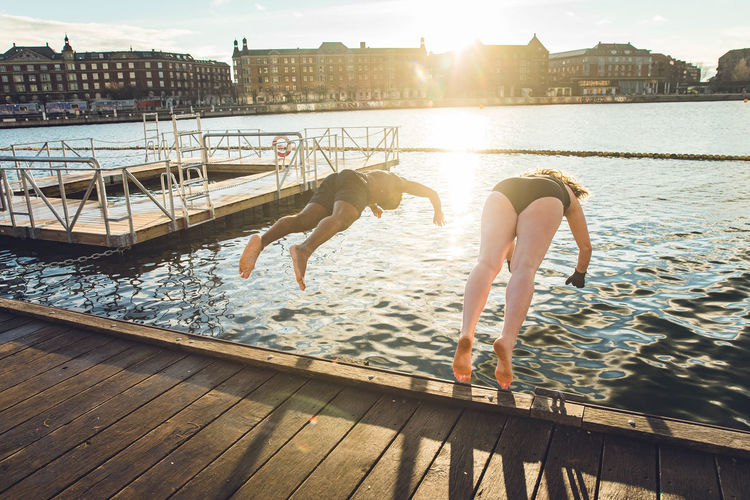 People at swimming pool by lake against sky