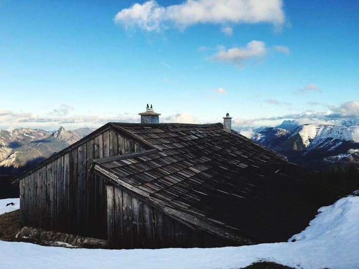 Old house on mountain during winter against sky