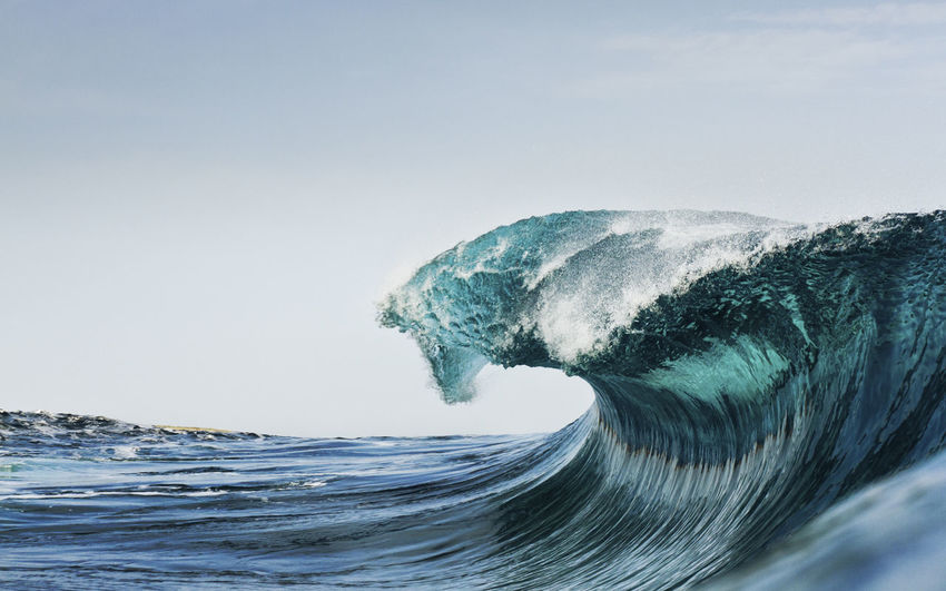 Breaking sea wave against clear blue sky