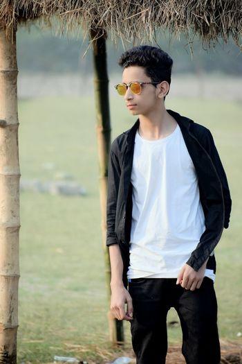 Teenage boy wearing sunglasses while standing on field