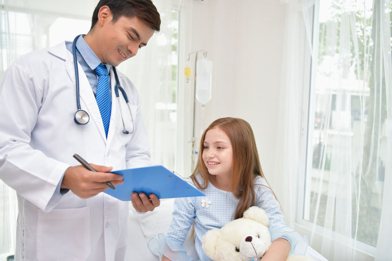 Doctor Showing Clipboard To Girl In Hospital