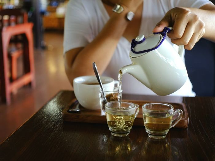Women who drink coffee at a coffee shop pouring hot tea from teapot into glass during break time. Cafeteria Asian  Background Aroma Taste Casual Caffeine Delicious Cozy Comfortable Beverage Food Familiar Refreshment Tasty Restaurant Fresh Lifestyle Healthy Herb Human Hand Happy Hour Bartender Drink Men Occupation Shot Glass Bar - Drink Establishment Filling Mixing