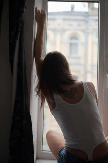 Rear view of woman sitting by window at home