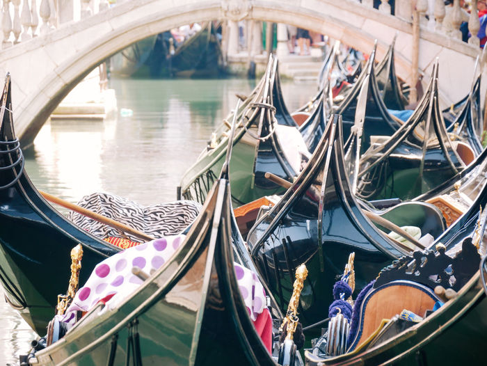 Group of traditional gondolas moored on narrow canal in venice