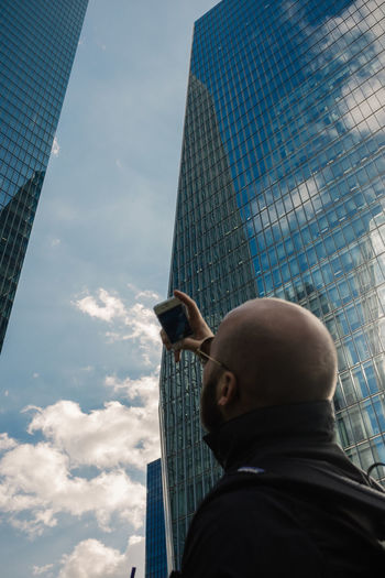 Low angle view of man taking selfie on mobile phone against modern buildings and sky