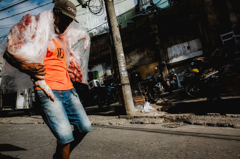 Super market employee carrying a pig on his shoulders Butcher Worker Working Working Hard Animal Meat! Meat! Meat! Pork Pig Market Dead Animal Documentary Documentary Photography Slum Favela Brazil Rio De Janeiro Men Hot Weather City Casual Clothing