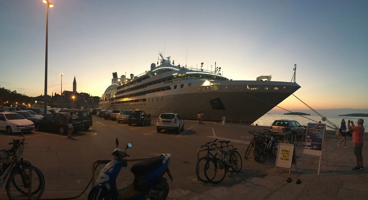 transportation, mode of transportation, sky, architecture, travel, sunset, water, nature, bicycle, incidental people, street, city, built structure, travel destinations, real people, nautical vessel, land vehicle, men, group of people, building exterior
