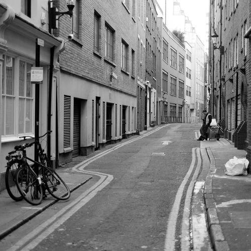 Man In City Street Between Residential Buildings