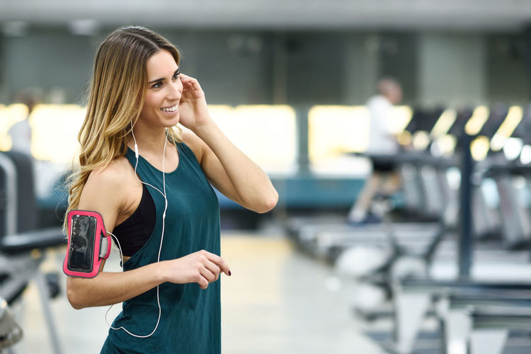 Woman Listening Music While Standing In Gym