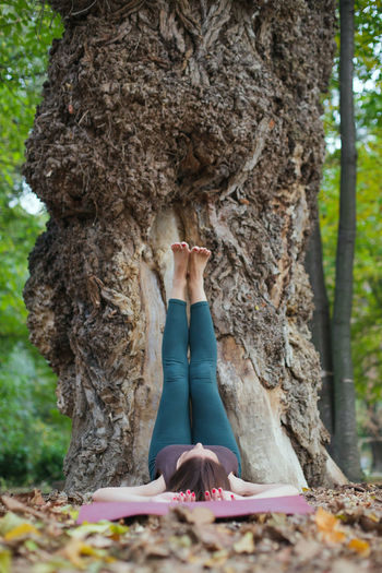 Woman standing on tree trunk