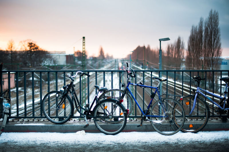 View of bicycles on bridge during winter against sly