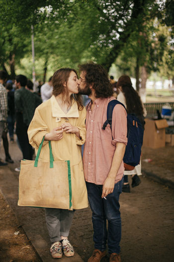 Couple kissing while standing at park