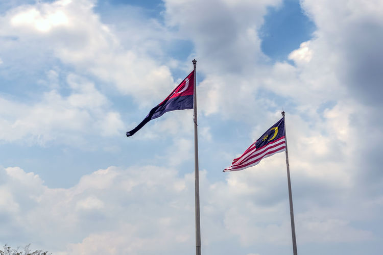 State flag of Malaysia And Johor bahru Flag.Malaysia flag also known as Jalur Gemilang wave with the blue sky. People fly the flag in conjunction with the Independence Day celebration or Merdeka Day.Johor Bahru is One of the states under the administration of malaysia Cloud - Sky Day Emotion Environment Flag Freedom Independence Low Angle View National Icon Nature No People Outdoors Patriotism Pole Pride Red Sky Striped Waving Wind
