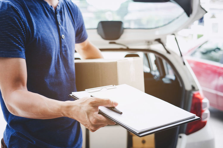 Midsection of man holding clipboard while delivering order