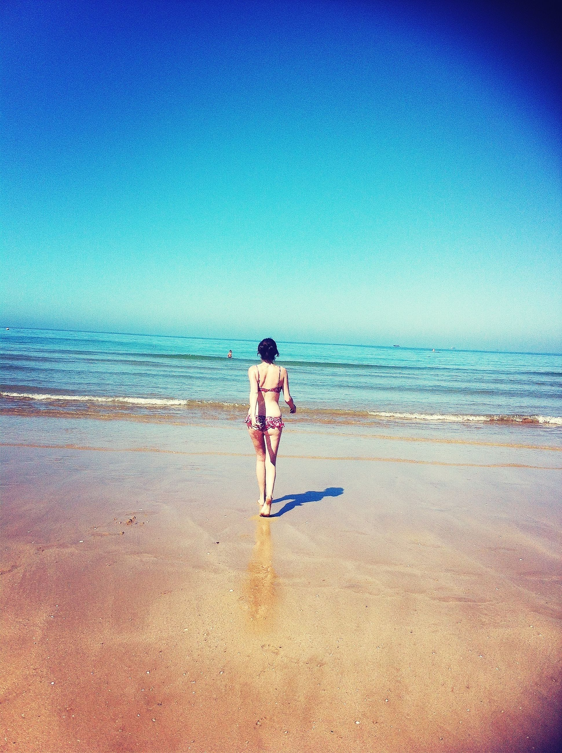 beach, sea, sand, shore, horizon over water, water, full length, leisure activity, lifestyles, tranquility, clear sky, vacations, tranquil scene, copy space, scenics, rear view, beauty in nature, sky