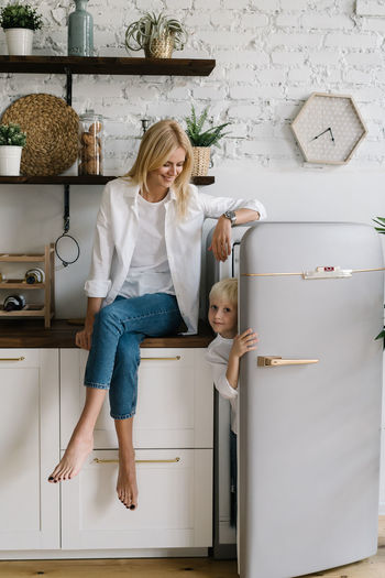 Portrait of son hiding in refrigerator while mother sitting on kitchen counter at home