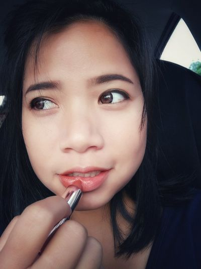 Close-up of young woman applying lipstick in car